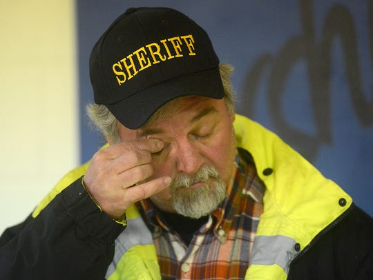 Sheriff Blair Weaver wipes his eyes during a news conference
