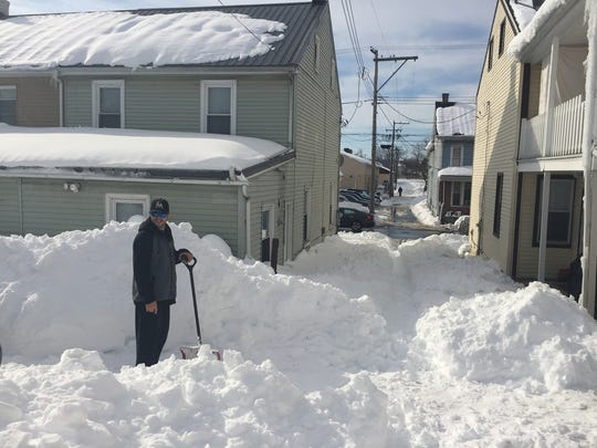 Jonathan Perugorria of Lebanon shovels a walking path from his home to South 10th Street along Linden Street where his vehicles are parked. Perugorria said Monday he does not expect to be able to drive until the street is plowed by the city of Lebanon.