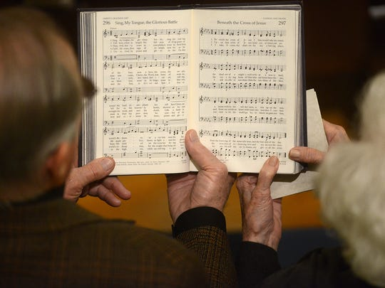 Jerry, left, and Ruth Ann Smith hold a hymnal together during the Holy Week Community Worship Service on Good Friday at First United Methodist Church.