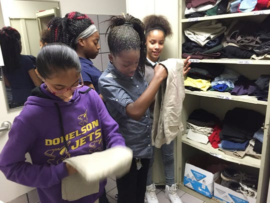 Donelson Middle sixth-graders Diya Patel, Keeli Redmond, Mikiya Woods and Andranique Voorhies fold and organize school uniform pieces in their school clothes closet.
