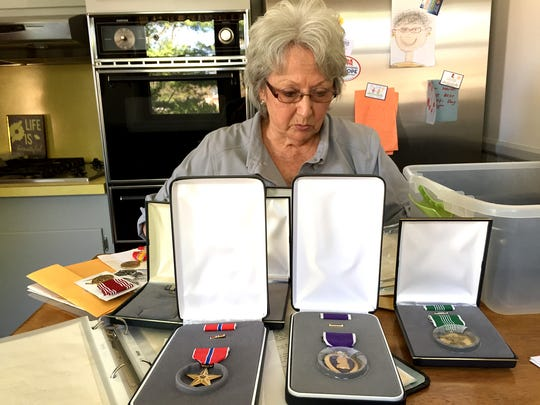 Gary Neiman's sister, Dot Rohrbaugh, tells her brother's story at the kitchen table of her Conewago Township home. In the foreground are the medals her brother earned after his death.