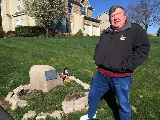 Pat Beckum stands by the memorial he erected in the front lawn of his Red Lion home to honor the men from his unit who died while he served in Vietnam.