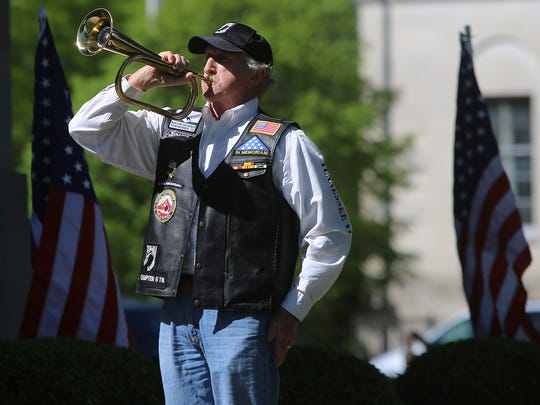 Ron Cheatham performs taps after the Missing Man Ceremony in front of the Madison County Courthouse on Friday morning.