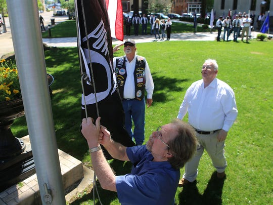 As Rolling Thunder Tennessee VI President Jim Phelps, center, and Mike Winslow, right, look on, Eric Skinner raises the POW-MIA flag donated by Rolling Thunder Tennessee VI on the flagpole outside of the Madison County Courthouse on Friday morning.