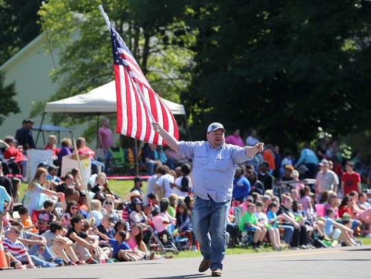 Gibson County Mayor Tom Witherspoon waves an American