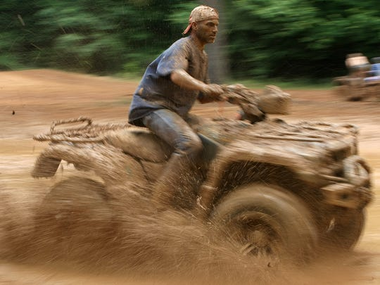 Mud flies up as Brian Richardson drives his ATV during Mudfest 2016 behind Donnie Matthews' home off of Lester Chapel Road on Saturday, June 4.