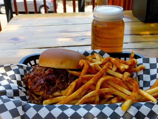 A pulled pork sandwich, seasoned fries and a local