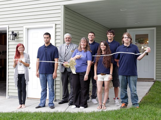 Fresh Start workers and future home owner Judi Balson cut a ribbon for the house at 359 Arlington Ave. From left to right are Aria Baade; Jordan Norton; Mike Bonertz, executive director of ADVOCAP; Balson; Todd Pusser; Aubrey Kraus; Dominick Gonzalez; and Alex Schmidt.