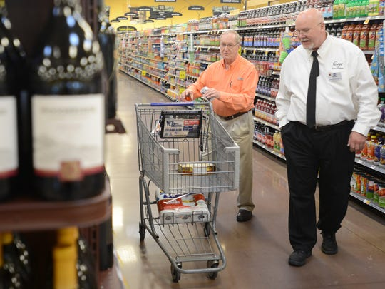 Charles Blankenship, center, gets help from Kroger wine specialist Randy Kail at the Kroger on University Parkway, on Friday, July 1, 2016.