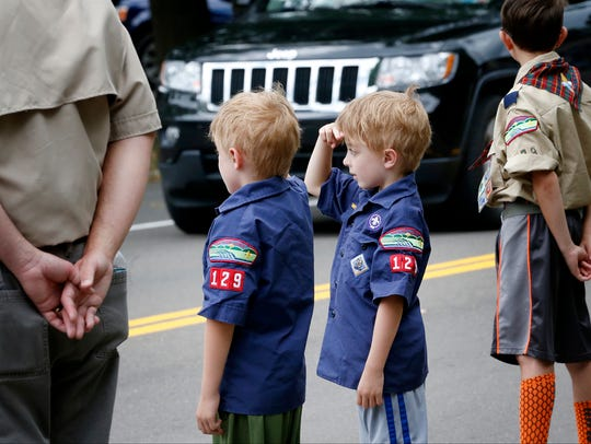 Scouts from Troop 129 salute the funeral procession