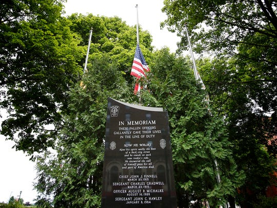 Flags hidden behind foliage at the Elmira Police Fallen Officers Memorial in Wisner Park fly at half-staff Tuesday in memory of the five Dallas officers killed on July 7.
