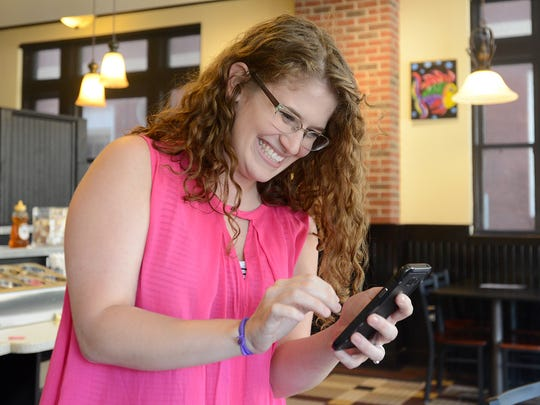 Woodstock Bake Shop employee McCall Scott reacts during a Pokemon Go gym battle at Woodstock on the Square in downtown Jackson, on Wednesday, July 13, 2016.