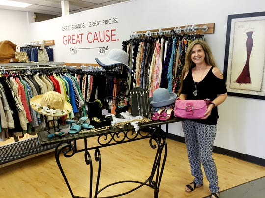Vickie Graham, manager of the YWCA's 2616 boutique, shows off a Coach purse that will be part of the storewide sale on July 23.