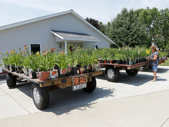 Three trailers full of potted plants greet visitors