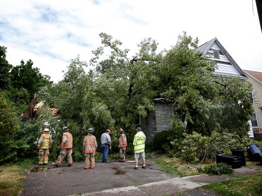 Southport firemen and a code enforcer survey the damage a tree caused when it crashed into a home in the 500 block of William Street in Southport Thursday.
