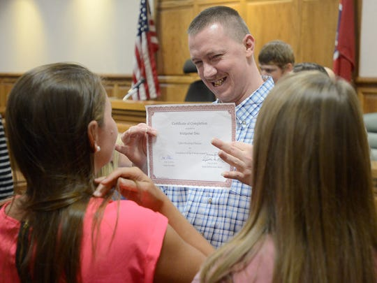 Kristopher Dies smiles as he holds up his Life's Healing Choices graduation certificate in Judge Don Allen's courtroom at the J. Alexander Leech Criminal Justice Complex, on Friday, July 15, 2016.