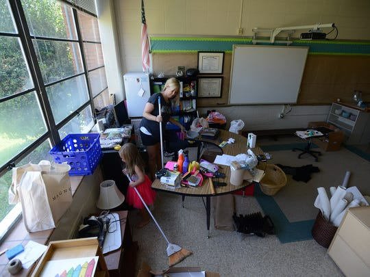 Rachel Turnbow and her 5-year-old daughter Hadley work on getting her classroom ready for the first day of school at the Community Montessori School on Monday, July 25, 2016.