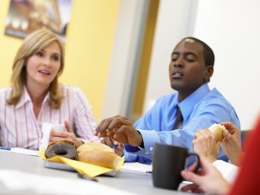Businessman reaching for donut at meeting