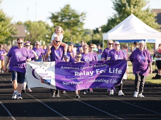 Cancer survivors take a lap around the track at Fond