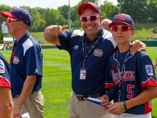 Maine-Endwell assistant coach Joe Mancini and Michael Mancini walk out of the opening ceremonies Thursday at the Little League World Series in Williamsport.