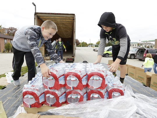 Garret and Isaac Glewen help unload a pallet of bottled