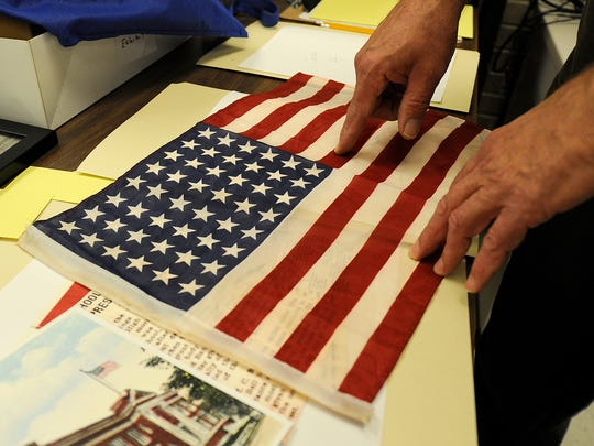 Library employee Jack Wood shows a replica 48-star flag at the Jackson-Madison County Library in Jackson, Tenn., on Wednesday, Oct. 26, 2016.