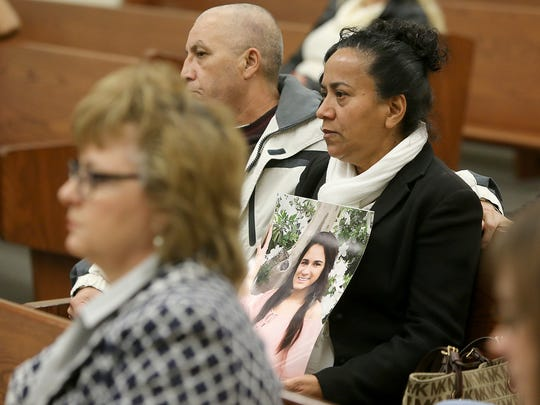 Sitting next to her husband, Angel Hernandez, Carmen Hernandez holds a picture of her daughter Elia during a preliminary hearing for Quin Love in Brownsville, Tenn.