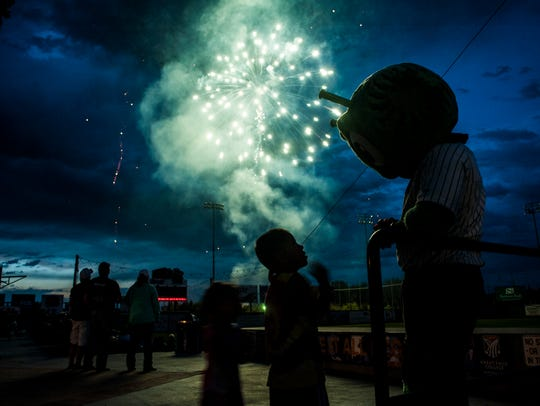A child looks up to Orbit, the Voyagers' mascot, as a fireworks display lights the sky at Centene Stadium.