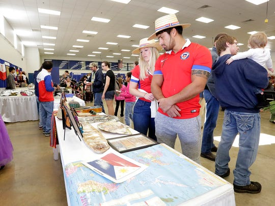 Sarah Courtney of Fond du Lac and Braulio Figueroa of Chile visit the Philippines booth at the 10th Celebrate Community festival at the Fond du Lac County Fairgrounds Saturday, Feb. 18. About 30 different countries were represented.