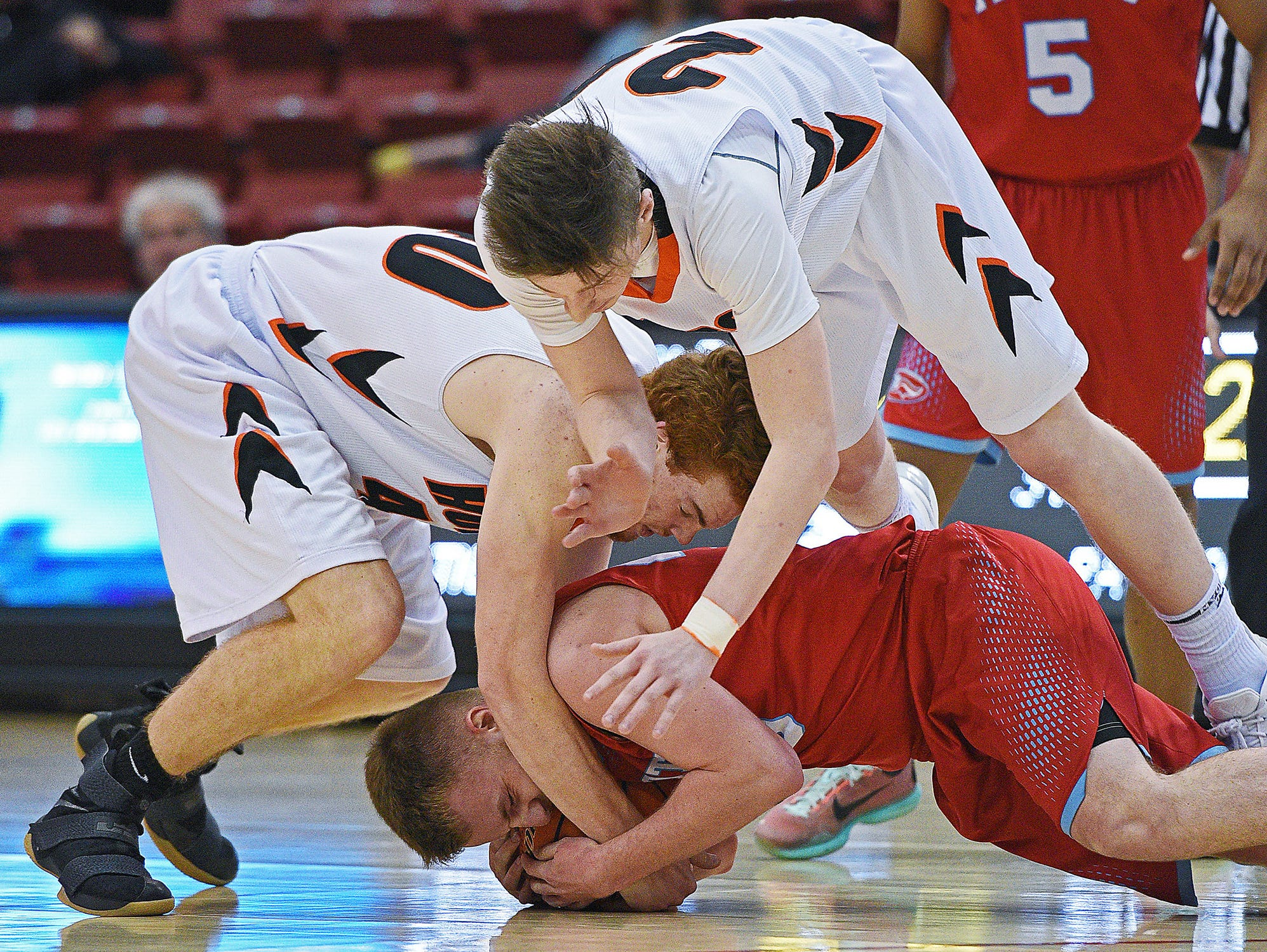 Lincoln's Andrew Tverberg (43) and Huron's Tye Evers (40) and Kobe Busch (24) struggle for the ball during a 2017 SDHSAA Class AA State Boys Basketball quarterfinal game Thursday, March 16, 2017, at Rushmore Plaza Civic Center in Rapid City.