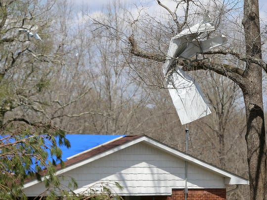 A piece of sheet metal rests in the branches of a tree near a home along Campground Road in Decaturville, Tenn., on Tuesday, March 28, 2017.