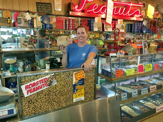 The Peanut Shop co-owner Olivia Swallows shows off a $2 bag of salted peanuts in this downtown institution located in The Arcade. .