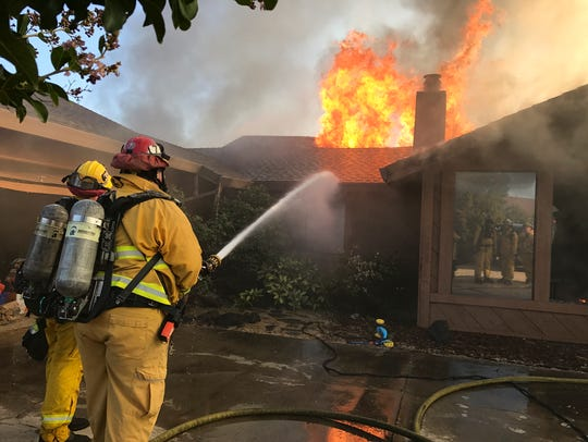 Redding firefighters work to save a home off of Teakwood