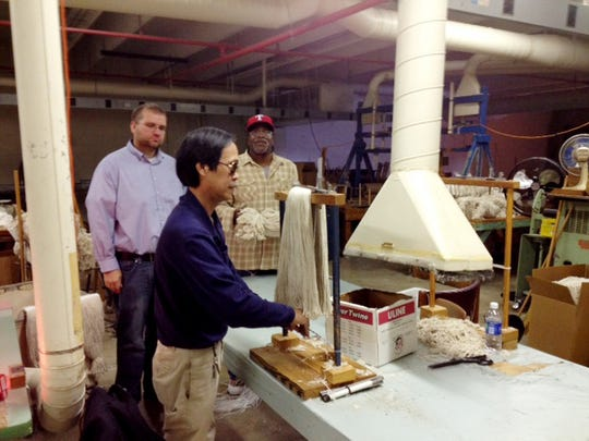 Phan Dung, front, makes a mop as plant manager Patrick Broughton, left, and Homer Sparks stand by at Ed Lindsey Industries for the Blind in 2013.