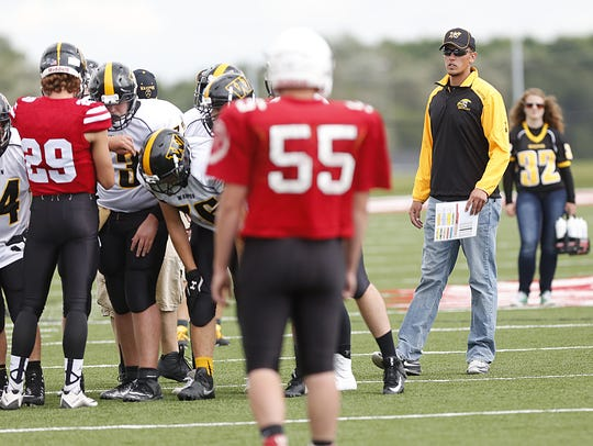 Ethan Kintzler, right, watches his team during a scrimmage