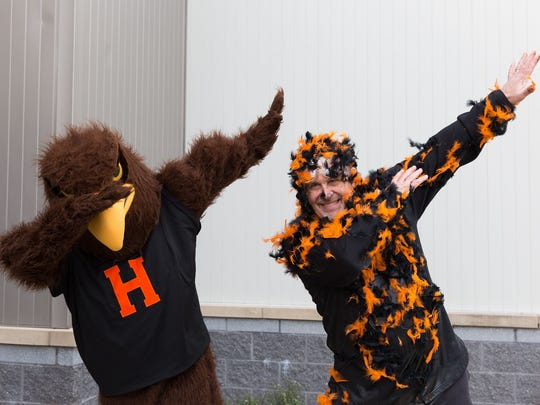 Clearview Elementary School principal Jay Czap and Hanover High School student Jarrett Klunk, dressed as the Nighthawk mascot, do the 'dab' after Czap was doused in syrup and feathers by second- and fourth-grade students at Clearview Elementary School after the school raised $1,038 in two weeks for Caring Hearts, a school program that helps families in need. Hanover's nickname of the Nighthawks dates back to at least the 1940s.