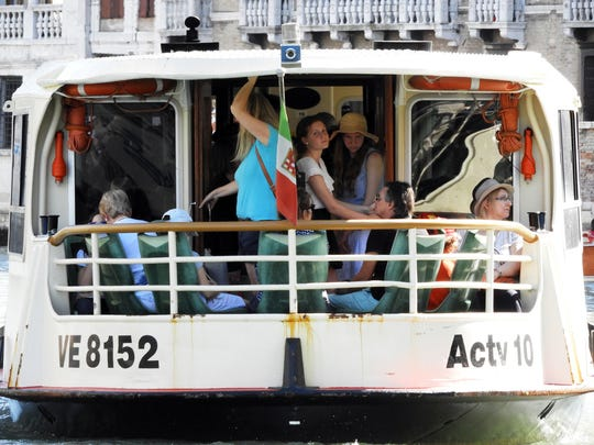 Tourists ride aboard a vaporetto, or public water bus, along the Grand Canal in Venice, Italy, this summer. Tourist overcrowding is a concern to city officials and residents.