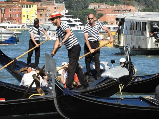 Gondoliers maneuver their tourist-laden crafts around