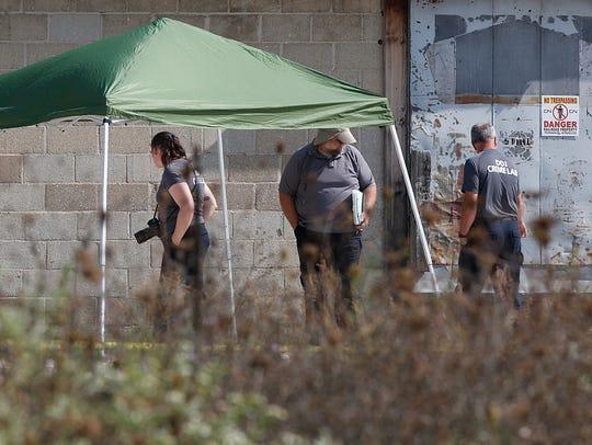 Department of Justice personnel investigate the scene