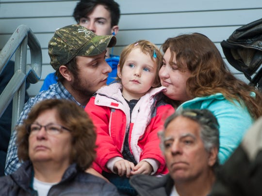 Isaiah Burk sits with his fiancŽe Ashlee Olson and her daughter Carmen Olson, 5, during the Veterans' Day Ceremony in Centene Stadium Saturday.