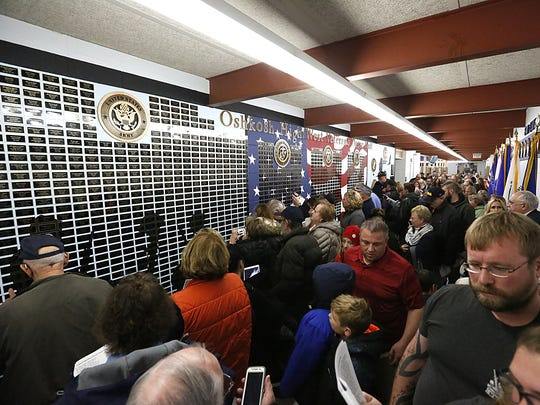 Crowds attending the Oshkosh High/West Veterans Honor Wall Commemorative Ceremony file through the hallway at Oshkosh West High School Saturday. The wall contains the names of all former students who have or are serving in the military.