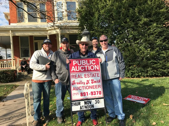 From the left in the back row, Joe Blanschan, Brandon Hershey Sr., Steve Cottrill Jr. Steve Cottrill Sr. of Budget Rentals LLC stand with auctioneer Bradley K. Smith in front of them after winning the auction Nov. 30 in front of 481 Madison Ave.