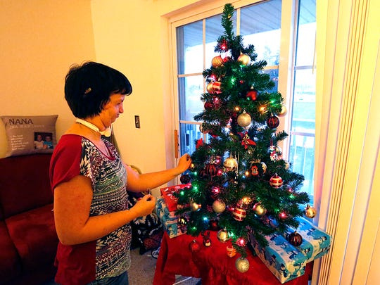 Sarah Freund of Fond du Lac places ornaments on her