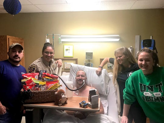 Officer Jeff Hughes poses with several friends who brought a care package to his room while he was being treated at United Regional Health Care System.
