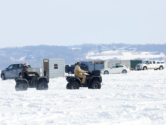 A pair of four-wheelers drive past sturgeon spearing