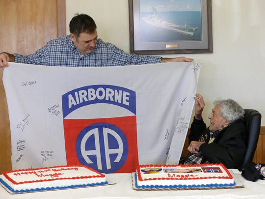 """Dan Packard of Lena, Ill., holds up a flag Saturday that was flown in Afghanistan and signed by the 82nd Airborne unit as a gift to WWII hero and Fond du Lac native James """"Maggie"""" Magellas at his 101st birthday celebration at the American Legion hall in Fond du Lac."""