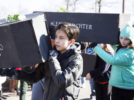 Gabe Robayo (left), 13, marches with a cardboard coffin in the first annual March For Our Lives in Audubon, NJ on March 24. Seventeen coffins were created to represent the lives lost in the Parkland school shooting on February 14, 2018.
