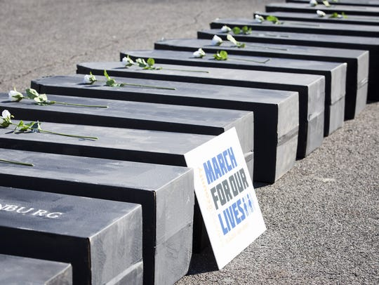 Seventeen cardboard coffins are placed in the parking