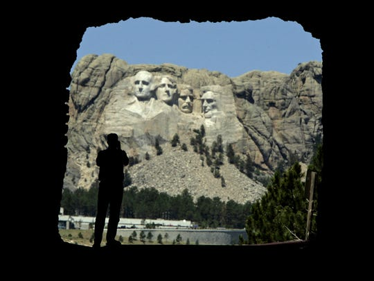 Gary Randol, from St. Peters, Mo., watches from a highway tunnel as workers pressure wash the granite faces of president George Washington, from left, Thomas Jefferson, Theodore Roosevelt and Abraham Lincoln at Mount Rushmore National Memorial in South Dakota, July 20, 2005.