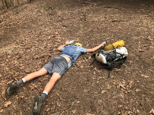 """Lance Ness, 31, collapses in relief after navigating a 3,000-foot climb that was """"pretty much straight up"""" on the first warm day of his Appalachian Trail thru-hike near the North Carolina-Tennessee border."""
